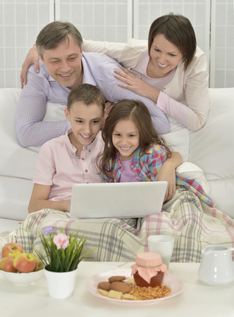 family  room: Portrait of a happy family with laptop in room Stock Photo