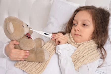 sniffle: Sad sick little girl lying in the bed with teddy bear toy
