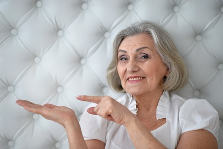 amiable: happy Senior woman portrait pointing at copy space Stock Photo