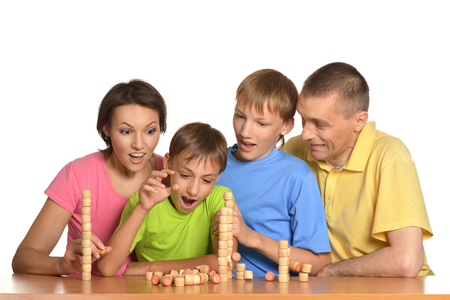 lotto: Family of four people playing lotto sitting at table Stock Photo