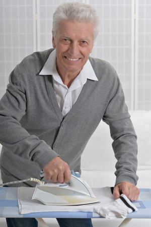 amiable: Portrait of a senior man during ironing