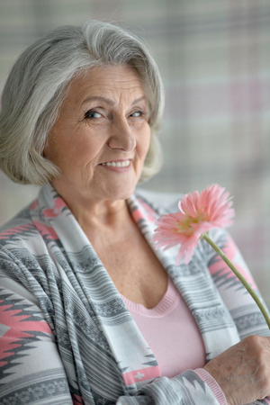 amiable: Portrait of a happy senior woman with flower