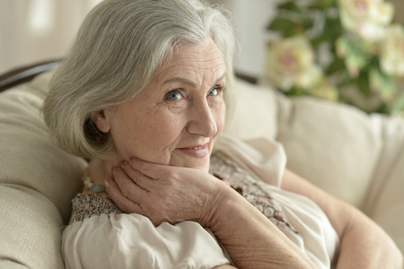 amiable: Portrait of a happy senior woman resting at home Stock Photo