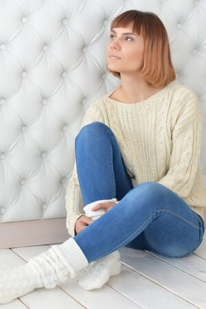 Beautiful redhead girl sitting on floor wearing sweater and jeans Stock Photo