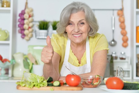 grey haired: Senior woman with grey hair cooking in kitchen with thumb up Stock Photo