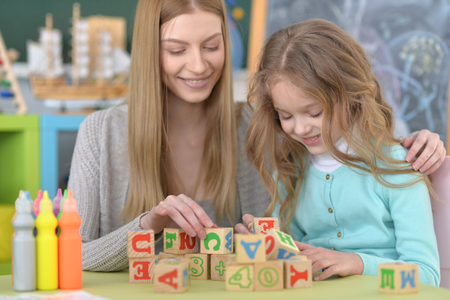 beautiful teacher: Beautiful teacher with pupil playing with cubes at school