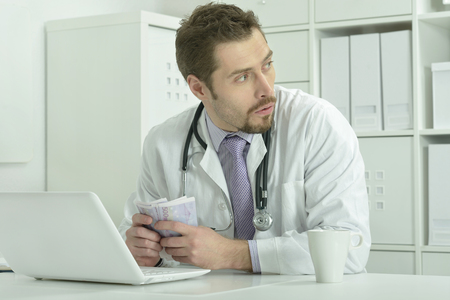 doctor money: portrait of young doctor with laptop and money Stock Photo