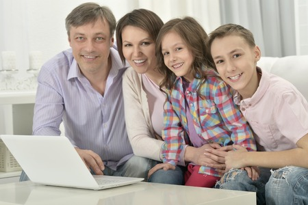 family  room: Happy family with laptop in a room Stock Photo
