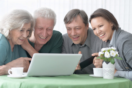 amiable: Portrait of a happy smiling family with laptop