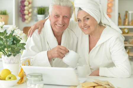 bathrobes: happy senior couple in a bathrobes with laptop  at home Stock Photo