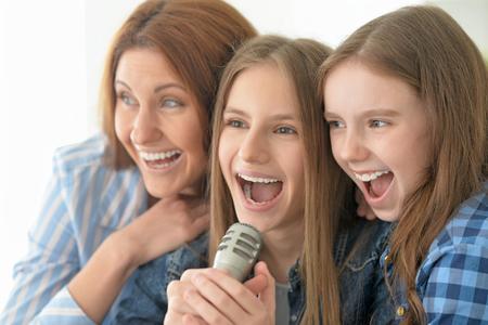 Portrait, heureux, mère et filles chantant karaoké