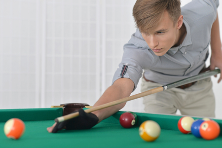 snooker rooms: Young man playing billiards in  billiard club Stock Photo