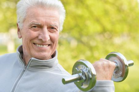 fitness hombres: Anciano ejercicio con pesas en el parque