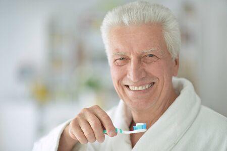 elderly man  brushing his teeth in bathroom Imagens