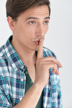 shush: man in a casual style  puts finger on her lips