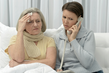 alarming: ill Senior woman with caring worried daughter  with phone