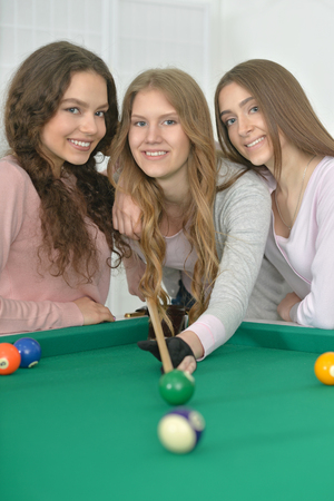 cue: Portrait of a young girls with cue playing billiard