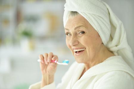 bejaarde vrouw haar tanden poetsen in de badkamer Stockfoto