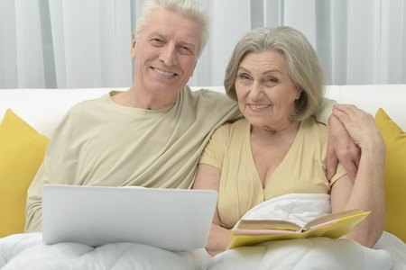 amiable: Senior couple resting and reading in bed Stock Photo