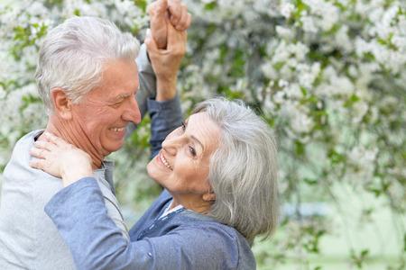 mujeres mayores: Bonita pareja madura bailando en el parque de la primavera Foto de archivo