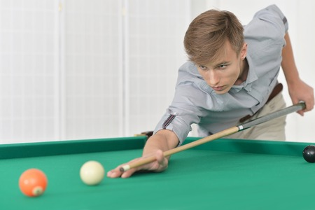 billiards room: Young man playing billiards in  billiard club Stock Photo