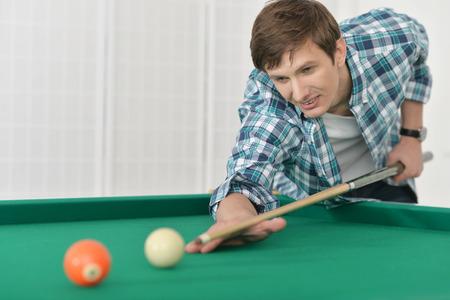 billiards hall: Young man playing billiards in  billiard club Stock Photo