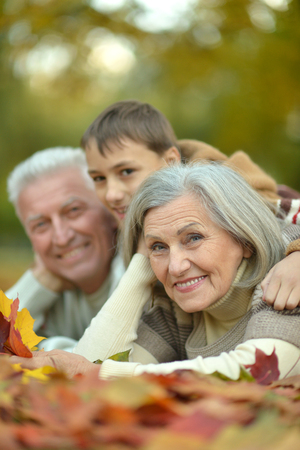grandson: Grandparents and grandson together in autumn park Stock Photo