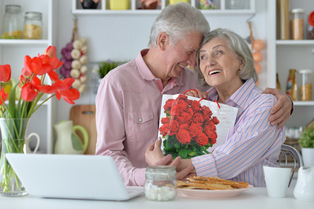 portrait  of Senior man gives  woman a gift