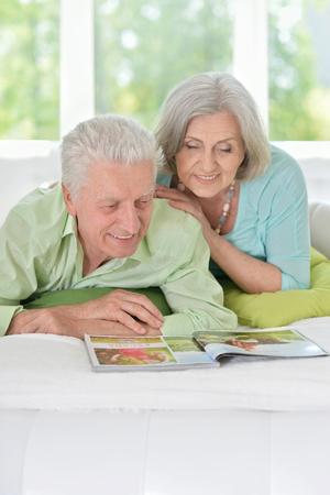happy Senior couple with magazine at home
