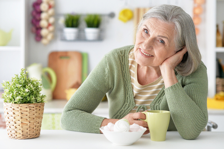 amiable: happy Senior woman portrait at table with tea cup Stock Photo