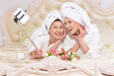 bathrobes: beautiful young women wearing a white bathrobes doing selfie Stock Photo