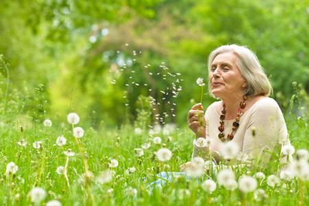Portret van een mooie senior vrouw in groen veld met paardebloemen