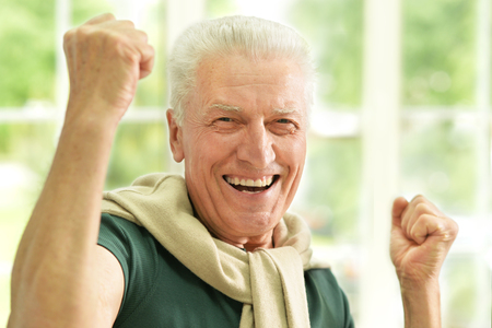 old man happy: happy Senior man  at home with hands up