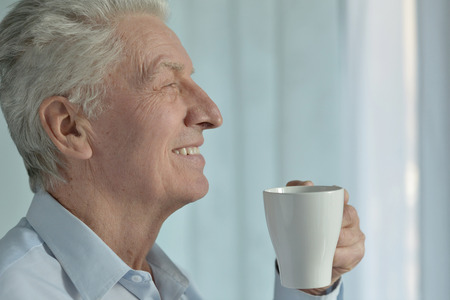 amiable: Portrait of a happy senior man with cup Stock Photo