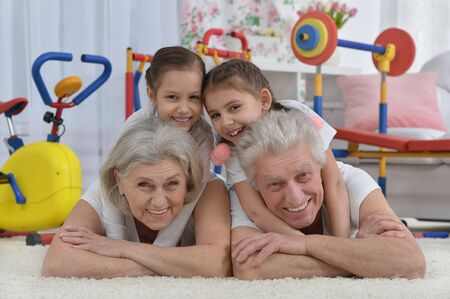granddaughters: grandparents  and  little granddaughters doing exercise home Stock Photo