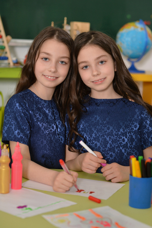 pencils  clutter: Cute schoolgirls twins on lesson of art at school Stock Photo