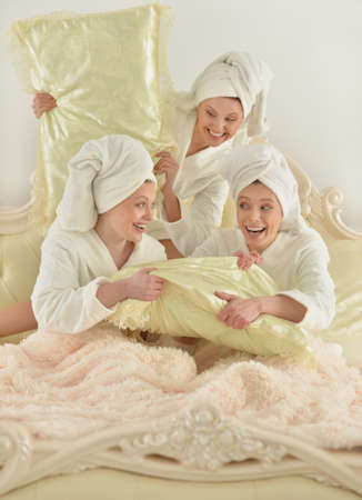 bathrobes: beautiful young women wearing a white bathrobes in bed Stock Photo