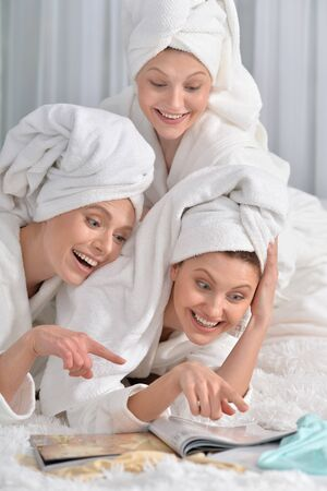bathrobes: beautiful young women wearing a white bathrobes with magazine