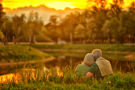 Loving mature couple  in summer park on the Sunset