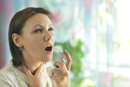 sniffle: Portrait of a woman squirting throat close up Stock Photo