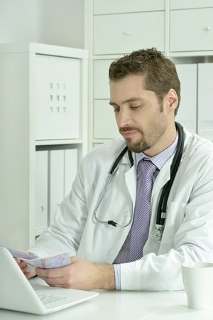 doctor money: Medical doctor working with laptop and money in the office Stock Photo