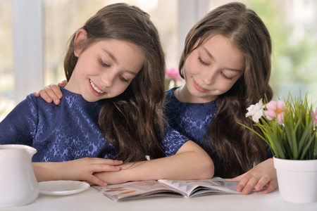 Portrait of couple brunette little twin girls reading a magazine Stock Photo