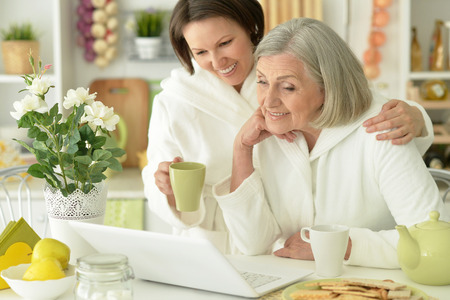 bathrobes: Senior woman and  daughter  in a bathrobes with laptop and tea Stock Photo