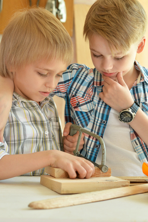 boyhood: cute little boys  working with wood in  workshop