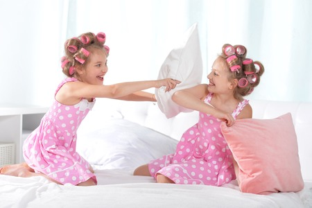 hair curlers: Cute  tweenie girls  in hair curlers playing with pillows with  at home