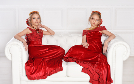 portrait of beautiful  little girls in red dresses  in studio