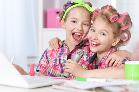 hair curlers: Cute  tweenie girls  in hair curlers  with laptop and  microphone  at home Stock Photo