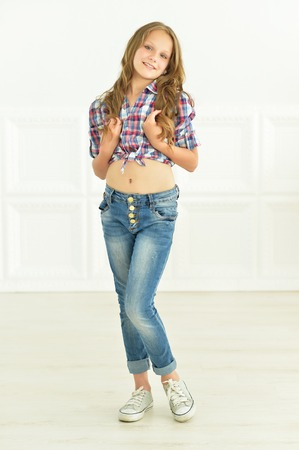 cute little girl posing in shirt and jeans in studio Imagens