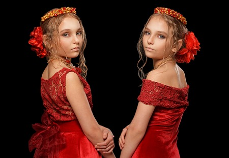 preadolescent: portrait of beautiful  little girls in red dresses  on black background