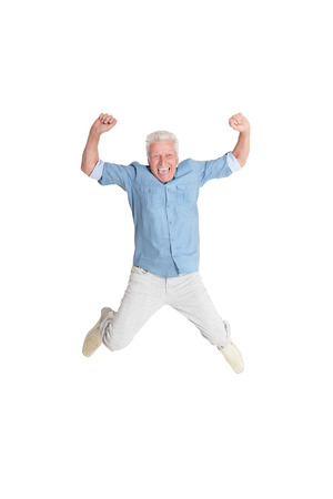 happy senior man in shirt jumping with hands up on white background